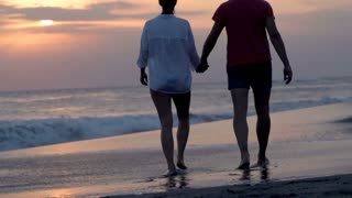 Couple walking on the beach during sunset and holding hands, steadycam shot, slo