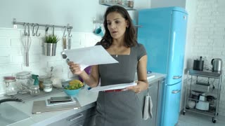 Elegant businesswoman looks worried while checking documents in her modern kitch
