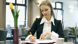 Elegant businesswoman writing on papers in the cafe and smiling to the camera, s
