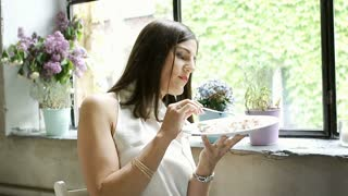 Elegant woman eating delicious dessert in the cafe and smiling to the camera, st