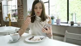 Elegant woman eating dessert and looks thoughtful while using smartphone, steady