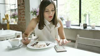 Elegant woman eating dessert in the cafe and browsing internet on smartphone, st