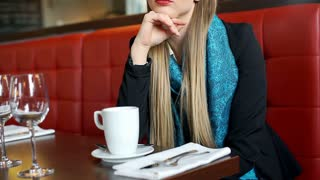 Elegant woman looks worried while sitting in chic restaurant and thinking about