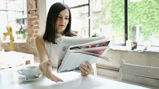 Elegant woman reading newspaper in the cafe and smiling to the camera, steadycam