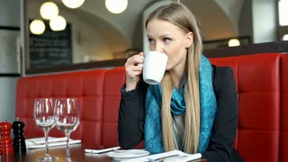 Elegant woman relaxing in chic restaurant and drinking coffee