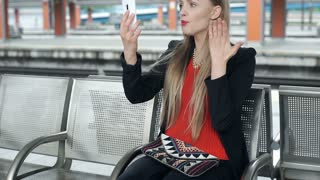 Elegant woman sitting on the station and having quarrelling with someone on vide