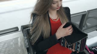 Elegant woman sitting on the station and texting messages on smartphone