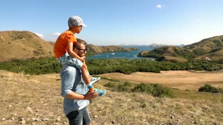 Father gives son a piggyback during hiking, slow motion shot at 240fps, steadyca