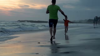 Father having fun with his son on the beach, steadycam shot, slow motion shot at