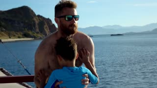 Father holding his son while standing on the boat, slow motion shot at 240fps, s