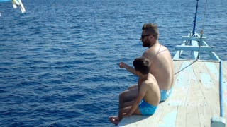 Father sitting with his son on the yacht, slow motion shot at 240fps, steadycam shot