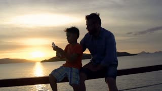 Father sitting with the son on balustrade during sunset, steadycam shot at 240fp
