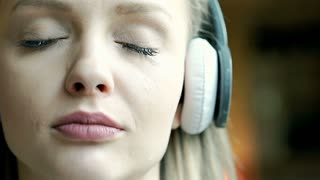 Girl crying and looks very sad while listening music, steadycam shot