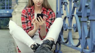 Girl in checked shirt wearing rollerblades and receiving bad news on smartphone,
