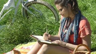 Girl looks irritated while writing in her diary, steadycam shot