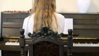Girl playing the piano and get the swing of it, steadycam shot