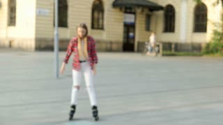 Girl riding on rollerblades in the city and hits her elbow, steadycam shot
