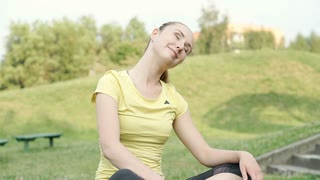 Girl sitting on the bench in the park and doing warm-up, steadycam shot