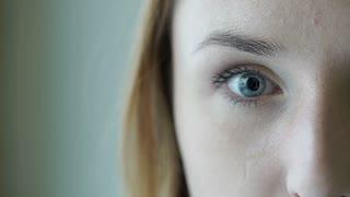 Girl's beautiful blue eye staring to the camera