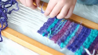 Hands of small boy weaving something from colorful wool on wooden loom