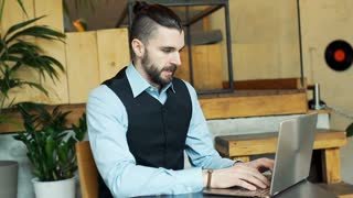 Handsome businessman working on notebook and looking to the camera, steadycam sh