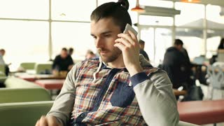 Handsome man answers cellphone and receives bad news, steadycam shot