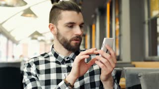 Handsome man checking something on smartphone and receives good news