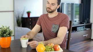 Handsome man drinking coffee and eating grapes while relaxing in the flat