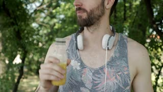 Handsome man drinking orange juice and showing thumb up to the camera, steadycam