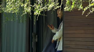 Handsome man going outside and texting on smartphone, steadycam shot, slow motio