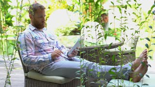 Handsome man having a videocall on tablet and relaxing in the garden