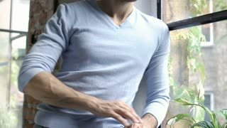 Handsome man having stomachache while sitting next to the window, steadycam shot