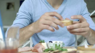 Handsome man in blue sweater eating lunch in the bistro, steadycam shot