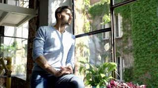 Handsome man in blue sweater sitting on window's sill and enjoys sunlight, stead