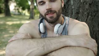 Handsome man in camis shirt sitting in the park and smiling to the camera, stead