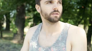 Handsome man in camis shirt standing in the park and relaxing, steadycam shot