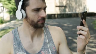 Handsome man in camis shirt wearing headphones and having a videocall on smartph