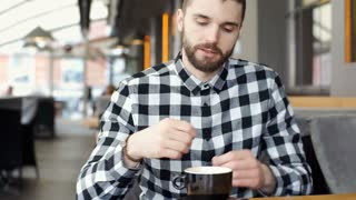 Handsome man in checked shirt drinking coffee and smiling to the camera, steadyc