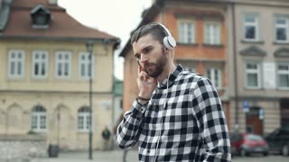 Handsome man in checked shirt listening music on headphones in the old town, ste
