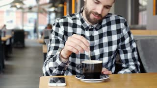 Handsome man in checked shirt mixing coffee in the cafe and eating mousse, stead
