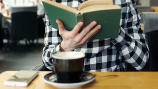 Handsome man in checked shirt relaxing in the cafe while reading book, steadycam