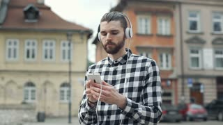 Handsome man in checked shirt standing in the old town and listening music, stea