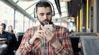 Handsome man in colorful shirt listening music on headphones and browsing intern