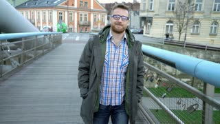Handsome man in jacket smiling to the camera while walking on the bridge, steady