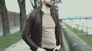 Handsome man in leather jacket standing on boulevards and smiling to the camera,