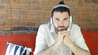 Handsome man in white shirt doing serious look to the camera and listening music