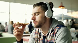 Handsome man listening music and eating pizza while smiling to the camera, stead