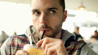 Handsome man looks happy while drinking orange juice, steadycam shot