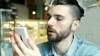 Handsome man looks happy while texting with someone on smartphone