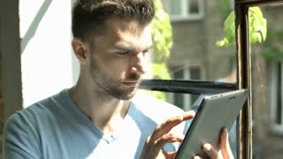 Handsome man looks shocked while reading news on the internet, steadycam shot